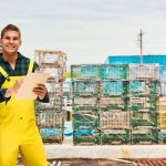 Fisherman writing on clipboard in shipping industry